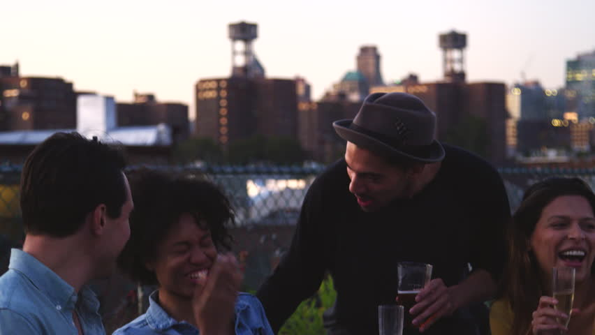 Happy friends talk and drink at a table on Brooklyn rooftop