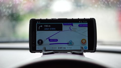 MALAYSIA, Kuala Lumpur, January 3, 2018: waze application on the smartphone shows the road direction on the car dashboard when the rains are visible in the windscreen  while the wiper works.