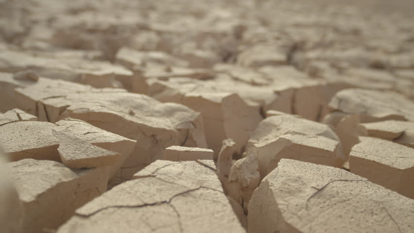 MACRO, DEPTH OF FIELD: Dry mud cracks shining in heat create an interesting landscape. Rugged rocky terrain providing no refuge for plants or animals. Global warming drying out once fertile land. | Shutterstock HD Video #34731910
