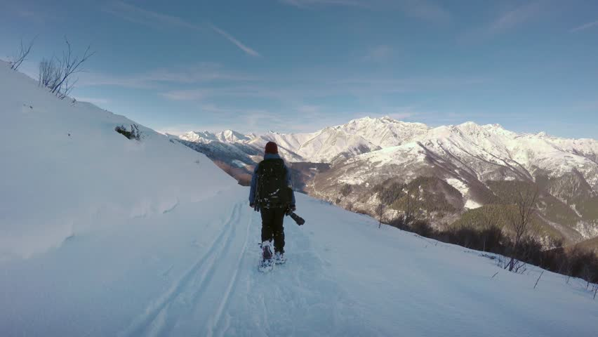 Following forward woman photographer hiking and walking by snowshoes on snowy trail path in winter.Alpine snow mountain outdoor activity.4k video #34733860