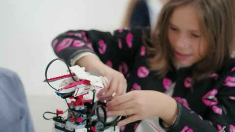 Girl teenager together boy constructing moving robotic model with remote control