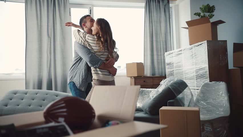 Nice Caucasian couple in love hugging and turning. Young people moving to new apartment. There are unpacked things, new sofa in living room.