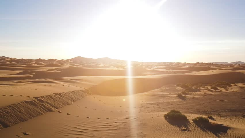 Sun shining on the sand dunes of Sahara desert while camera flies up to the sky