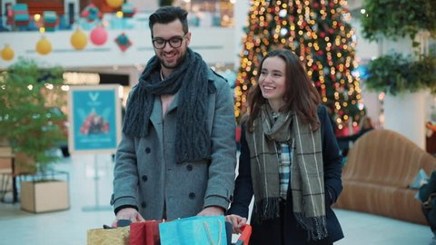 Young lovely couple with Christmas present walk in a mall smiling feel happy shopper family woman tree christmas shopping man shop store gift holiday shopping slow motion