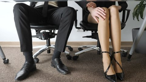 Office harassment. A young man in a suit is sexually harassing a beautiful girl in the office. Touching the girl for the knee