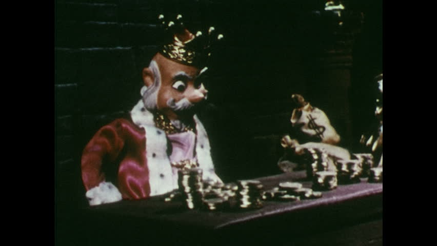1950s: King sits and claps hands. Man pulls piles of gold coins to himself and covers with his arms. King moves treasure around on table.