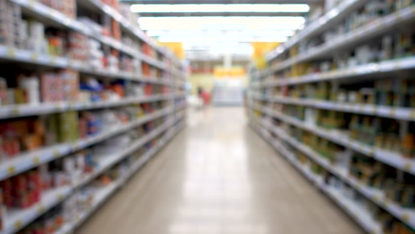 shop, blurred background, people with shopping carts. People are shopping in a supermarket, defocused blurred background