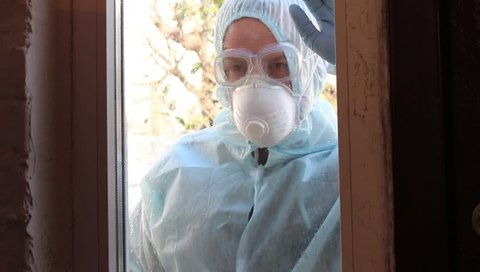 Control of epidemic- and pandemic-prone acute respiratory diseases. Personal protective equipment. A man knocks on the window