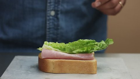 closeup of man's hand making sandwich, puts from sides all ingredients on plate