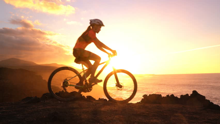 Mountain biking MTB cyclist woman cycling on bike trail at sunset by ocean. Person on bike by sea in sportswear with bicycle enjoying healthy active lifestyle in beautiful nature outside. | Shutterstock HD Video #34856470