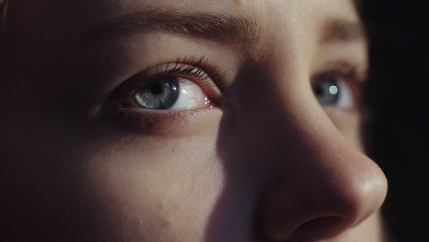 Extreme close up view of stunning blue-eyed woman opening her eyes, taking a deep breath and looking around. Slow motion