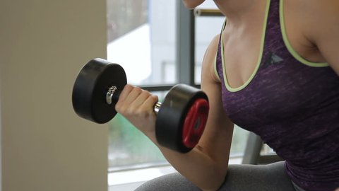 Young woman is doing biceps dumbbell curls in modern sports club. Attractive blonde is training with free weight in gym room. Female with pigtail and decollete, sits on bench near window and raises