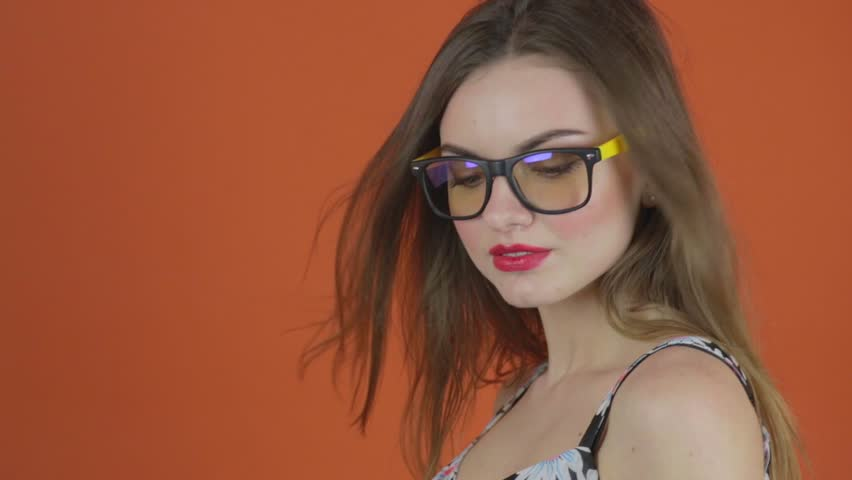 Attractive smart woman in glasses and flower dress glasses and looks sexy, orange background. Wind blows hair