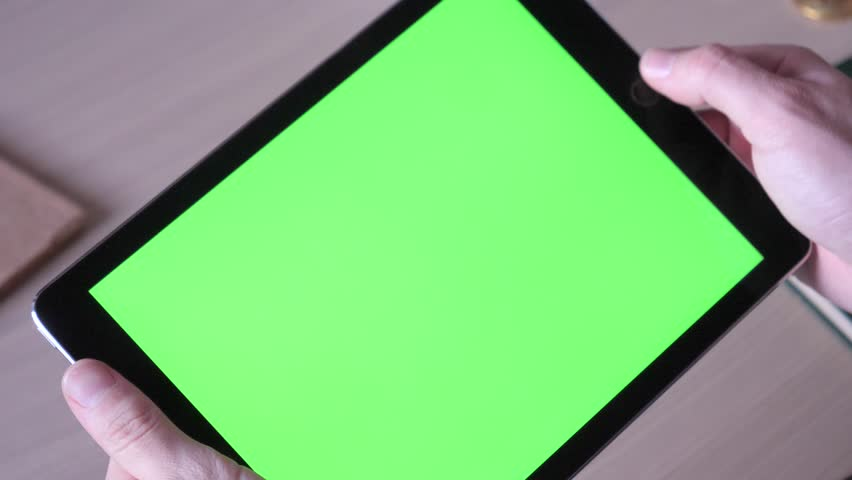 Tablet with green screen above a desk with a hand making gestures above it. #34895920