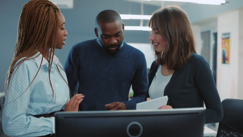 Three multicultural colleagues of different nationalities reviewing presentation before meeting. Young people discussing all details. Indoors. | Shutterstock HD Video #34937728