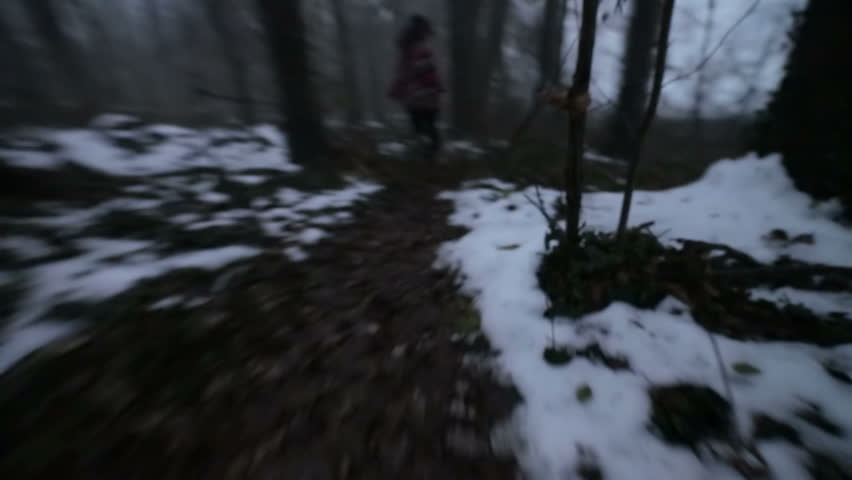 Girl trying to escape of someone who chase her in the dark forest of autumn