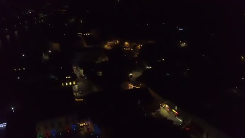 Aerial: Flying near small city at night. Lots of new year decorations lights shining and reflecting from river runing through town.
