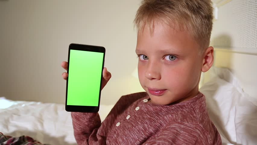 Mockup video of cute funny smiling kid laying in bed in home interior. Front view portrait of child holds modern mobile phone with blank green screen in hands. Boy looks at camera smiling. | Shutterstock HD Video #35009305