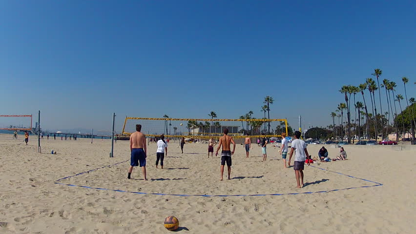 LONG BEACH, CA - February 23, 2013: A wide shot of young men enjoying a game of volleyball at the beach circa 2013 in Long Beach.