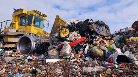Enviromet pollution concept. A low angle view on a landfill compactor moving trash.