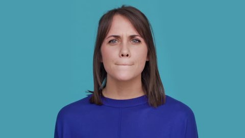 Portrait of concentrated brunette female 30s biting lips thinking about things doubting suddenly finding solution and putting index finger up over blue background. Concept of emotions