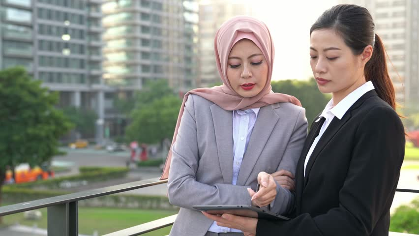 Asian Businesswoman showing tablet to business manager