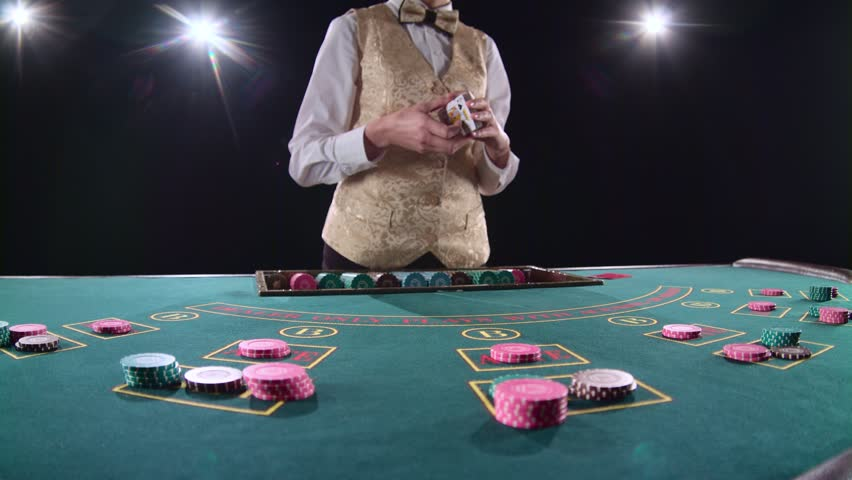 Casino professional croupier shuffles the poker cards and performing trick with cards. Black background. Bright light. Slow motion