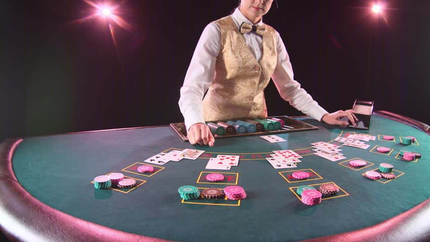 Casino dealer woman takes the cards from card holder for game in poker. Black background. Slow motion