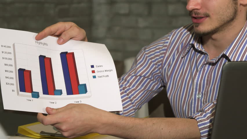 Cropped shot of a businessman showing printed diagrams on a business meeting | Shutterstock HD Video #35024353