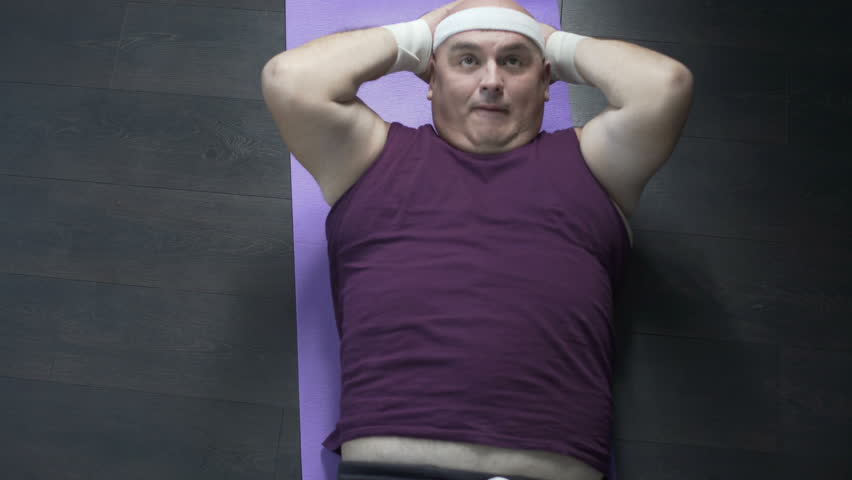 Obese person in sportswear doing crunches on floor mat at home, lazy workout | Shutterstock HD Video #35028100