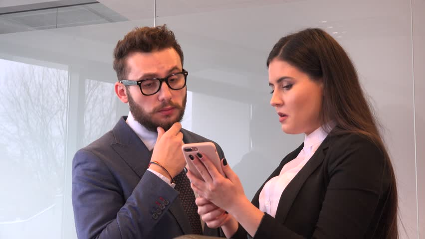 Young attractive business people stand by windows discussing cell phone news 4K | Shutterstock HD Video #35030080