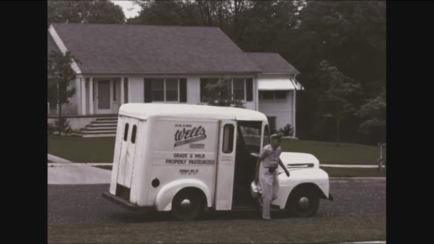 CIRCA - 1953 - A milkman delivers milk bottles to a porch and a housewife picks them up and brings them into her home.