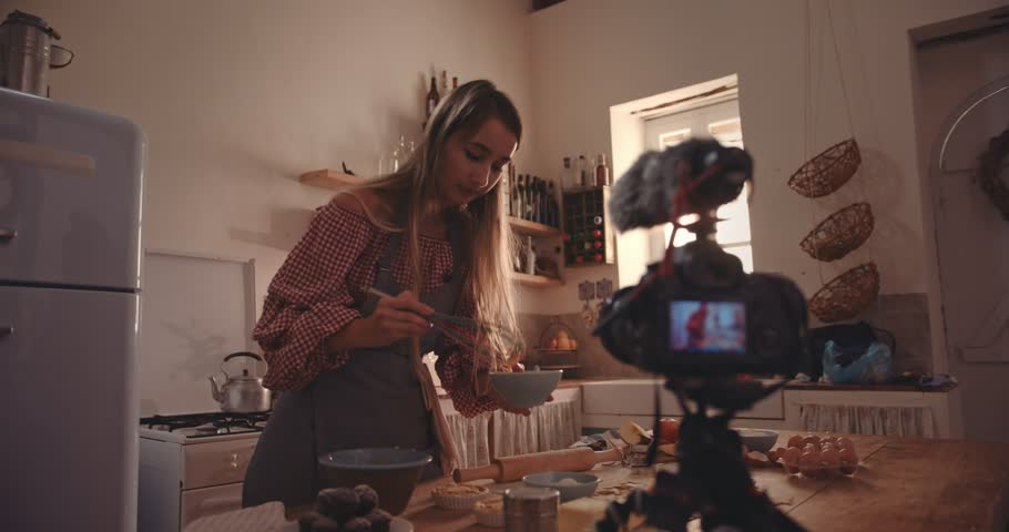 Female vlogger with food blog baking pies in rustic kitchen and recording video on camera | Shutterstock HD Video #35058580