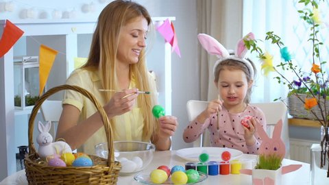 Happy Easter! Young mother and her cute little daughter wearing funny rabbit ears are coloring easter eggs sitting at a festive table with basket and Bunny. Slow Motion