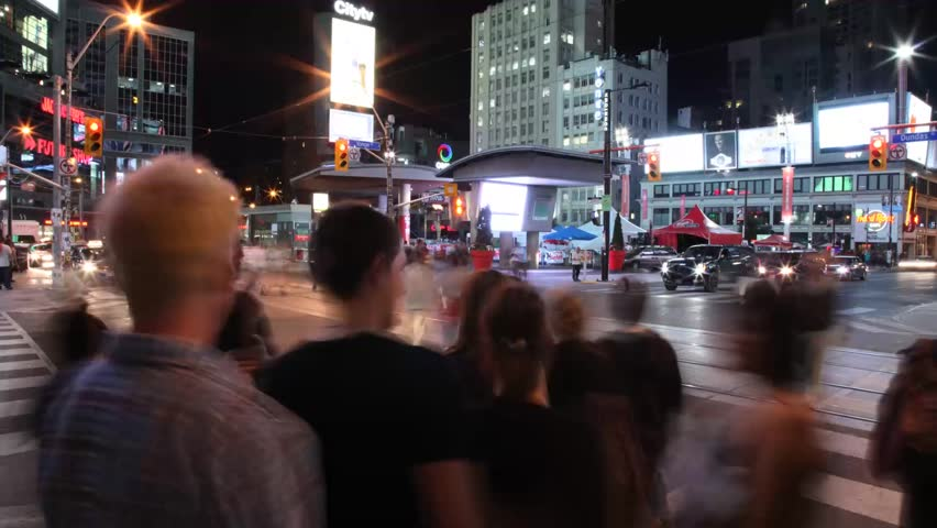 TORONTO - CIRCA 2012: Pedestrians and tourists cross through Yonge-Dundas Square. Since its completion in 2002, the square has established itself as a prominent landmark and prime tourist attraction.
