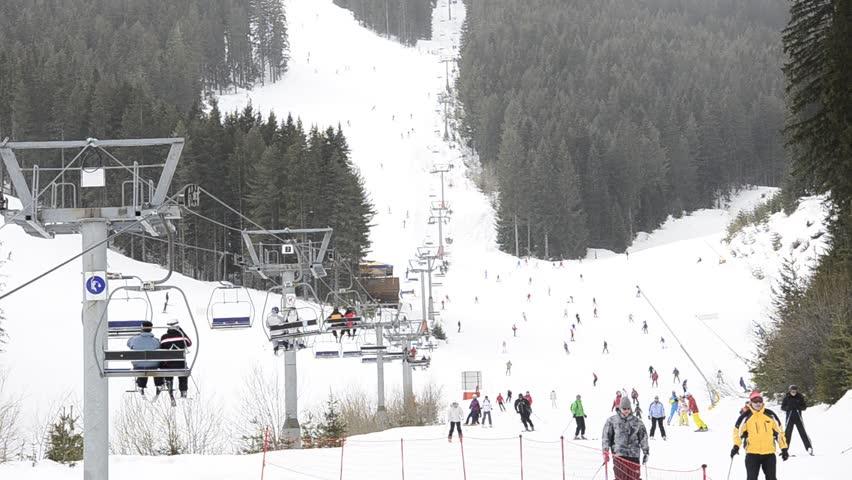 ski resort, chair ski lift elevator lifting people on the mountain ski slope, Bansko, Bulgaria ski centre