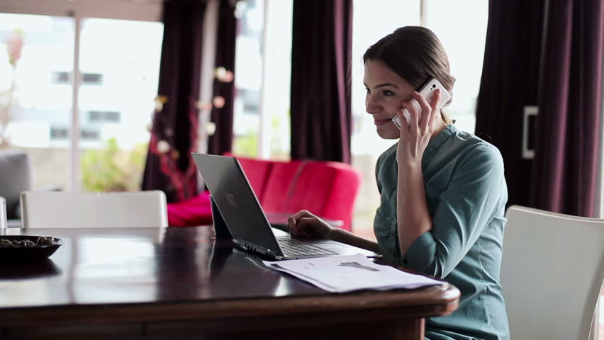Young businesswoman working with cellphone and laptop in home