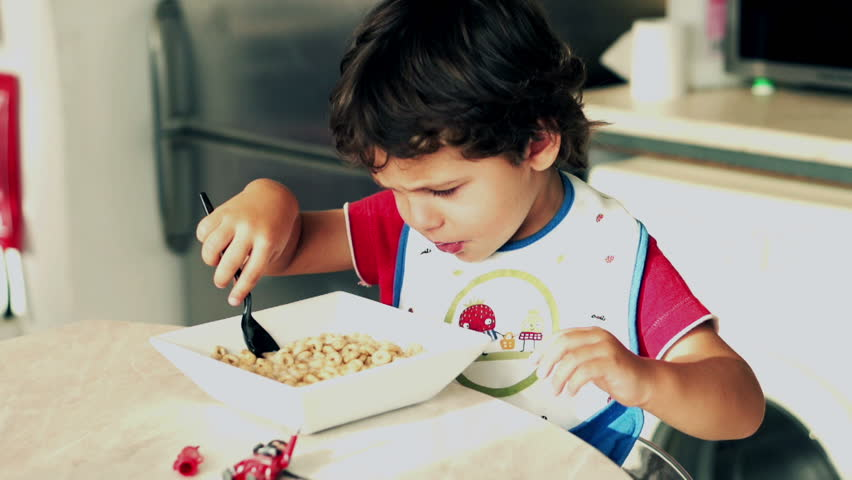 Little boy eating cornflakes with milk, slow motion shot at 240fps