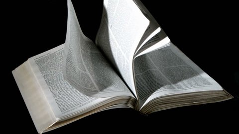 Bible pages turning in the wind on black background in slow motion
