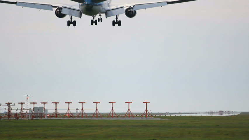 Commercial Jet Plane landing. A jet airplane. Landing gear down, runway markers in the foreground.
