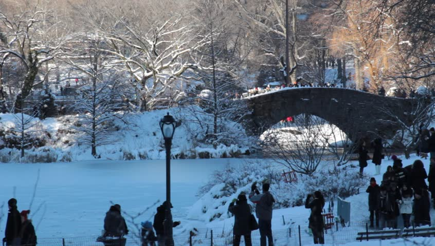 New York, NY - Circa 2011: People walk around in Central Park in Winter Snow during the day enjoy the sights and having fun