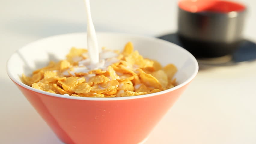 pouring corn flakes and milk inti a breakfast bowl with coffee cup in the background,shot taken with a wide aperture shallow dof