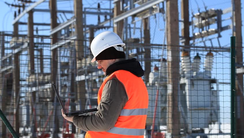 Electrician talking on the cell phone near at the electrical substation | Shutterstock HD Video #3568160