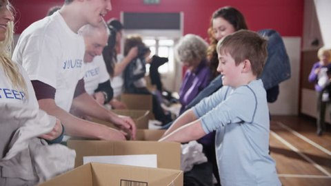 A cute young boy donates some groceries for a good cause and gets a high five from one of the volunteers. In slow motion.