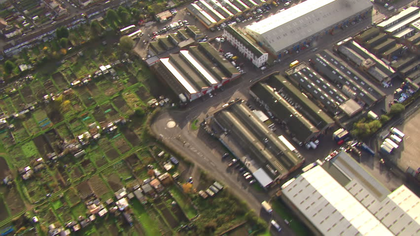 Aerial view over some fields and hedgerows and industrial buildings on the outskirts of London, England