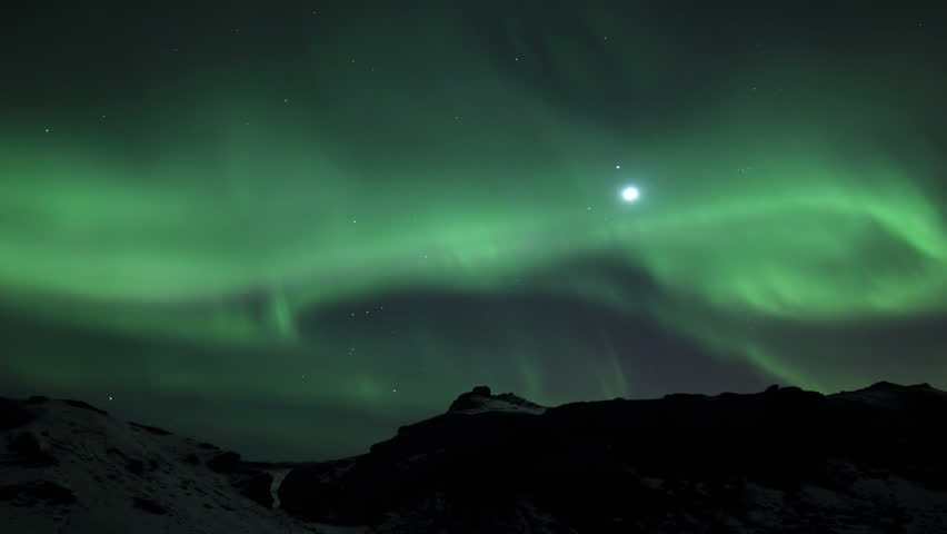Northern Lights in Lava Field, Reykjavik Iceland. Tourists can be seen walking on the lava field with the aurora overhead