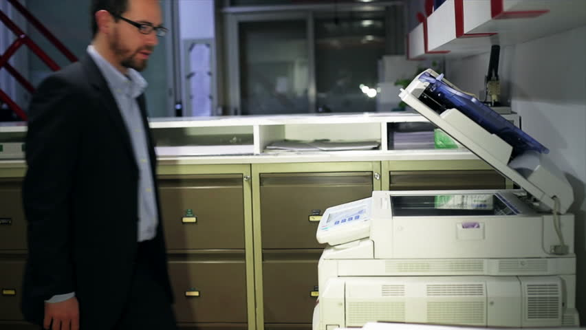 Male assistant makes copies of files with a copy machine