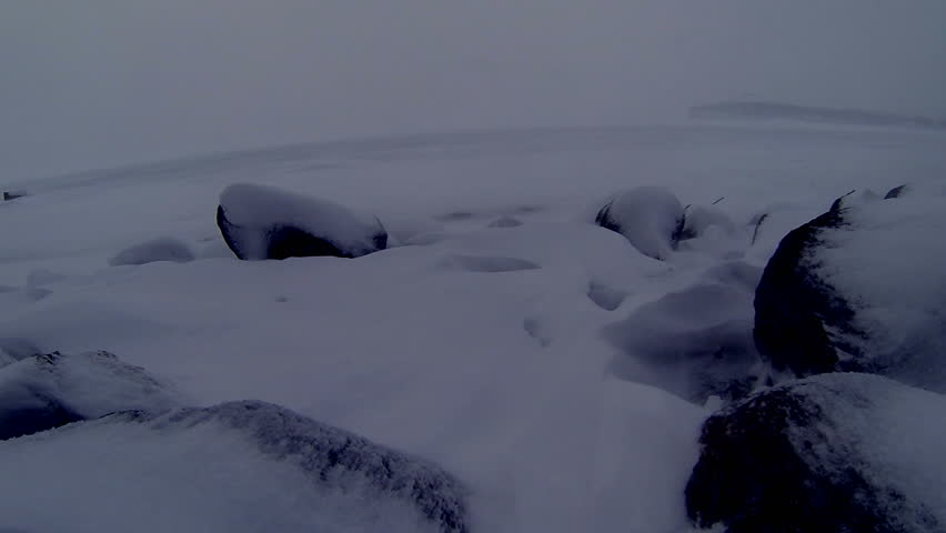 Snow blows towards the camera from across a wintry lake over rocks in the dim light of dusk. Slow motion video, shot at 60fps and conformed to 24fps (40% speed). Looping video.   Shutterstock HD Video #3605480