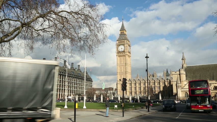 LONDON - MARCH 13: Red London bus passes Big Ben in Parliament Square on March 13, 2013 in London.