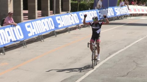 MONEGLIA, ITALY – SEPTEMBER 11: Single cyclist being applauded as he reaches the finish line on September 11 2011 in Moneglia